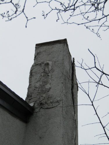 Major damage at stucco-covered chimney