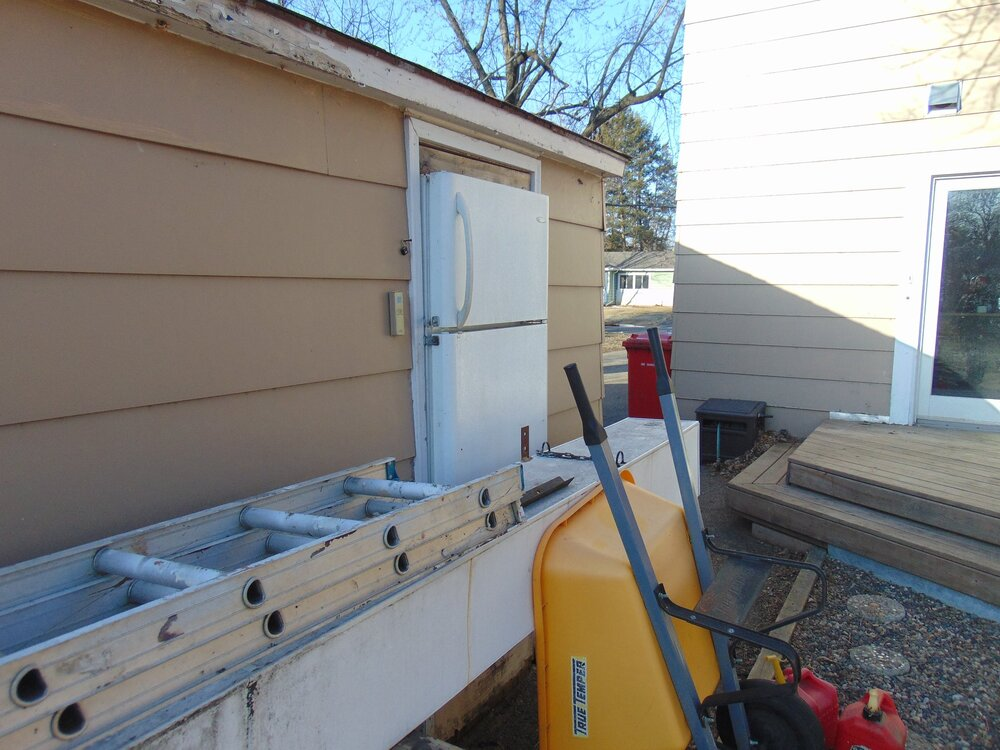Who throws the best yard parties? This guy. Yep, that's a fridge installed in the doorway of the garage.