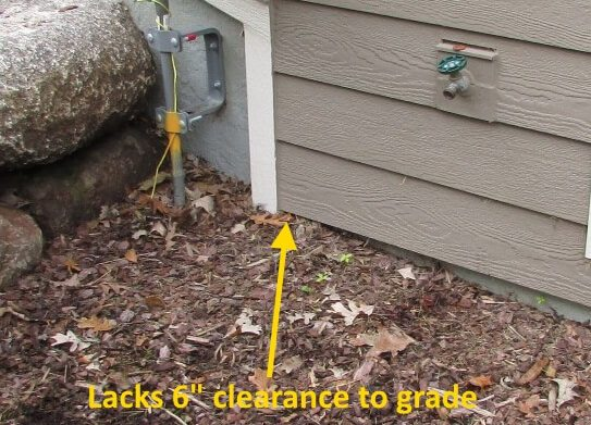 Lacks required clearance to grade